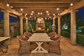 comfortable wicker chairs and wooden long table using sweet outdoor string lights for elegant patio decor