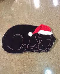 this is a wonderfully fun holiday rug featuring a sleeping black labrador wearing a santa hat it will definitely be a holiday hit