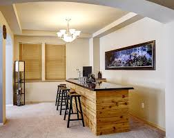 basement bar with wood countertop and aquarium accent wall