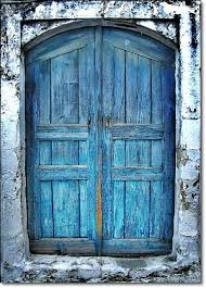 blue door on old building in crete greece photo by eleanna kounoupa