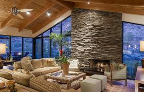 living room with stone fireplace. living room with glass walls and huge stone fireplace