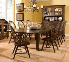 small rustic farmhouse dining room design with diy custom expandable large wooden dining table and 8 chairs under old black iron hanging chandelier ideas