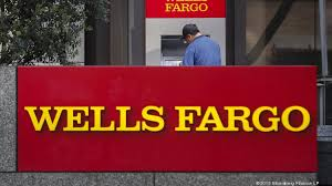 a man uses an atm outside of a wells fargo co bank branch in