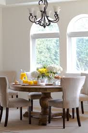 Elegant dining room iron chandelier and contemporary dining chairs and  large round pedestal dining table.