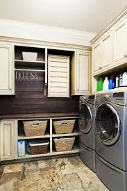 Laundry room Laundry room Ideas room like the idea of baskets lower, closed  cabinets higher - love the dark wood wall/backsplash with the ivory  cabinets.