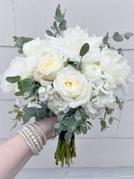 elegant white bridesmaid s bouquet composed of peonies stock garden roses ranunculus and eucalyptus designed at west view florist in elkhart in 46514