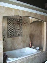 cozy stone tile bathroom with mosaic tile accent and chandelier also bathtub shower combo