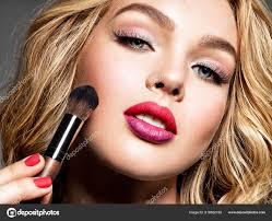 beautiful woman applying makeup makeup pretty blue eyes fashion stock photo