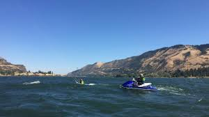a person on a jet ski follows a beginner kiteboarder on the columbia river