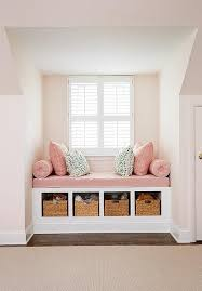 Pink girl's room features a nook filled with a built-in window seat fitted  with open cubbies filled with woven baskets topped with a dusty pink lin