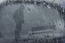 sad boy wearing hood standing in rain with bench
