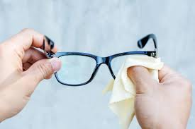 a person cleaning eyeglasses