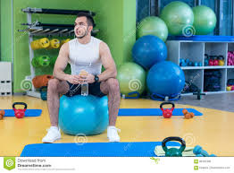 man sitting on a gym ball holding a phone after doing a work out