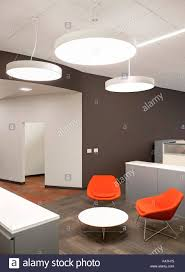 suspended office lighting. Main Office With Creative Lighting. Seating In A Lobby, Orange Chairs, Round Table And Discreet Desk. White Brown Walls. Suspended Lights Lighting G