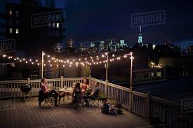 terrace lighting. Young People Sitting Under Fairy Lights At Roof Terrace Lighting