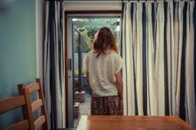 looking out door. Rear View Of Person Standing By Curtains French Doors And Looking Out Door H