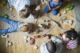 Overhead view fathers and children enjoying play date playing with toy train wood blocks The 7 Best Train Sets for Kids to Buy in 2019