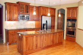 new kitchen with wood cabinets hardwood floors and stone countertops