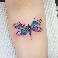 стрекоза с разноцветными крыльями тату на предплечье у девушки