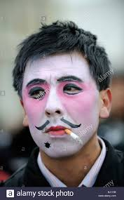 chinese man with theatrical makeup smoking while spring festival performing in yuxian i china 28 feb 2010