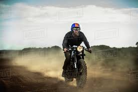 man wearing open face crash helmet and goggles riding cafe racer motorcycle on a dusty dirt road