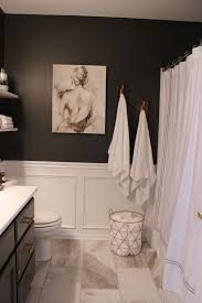 marble tiles black walls and white wainscoting for a refined bathroom