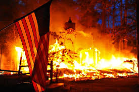 u s department of > photos > photo essays > essay view a u s flag hangs in front of a burning structure in the black forest fire in