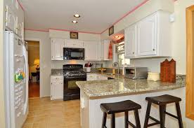 black laminated wooden kitchen island white painting cabinet stainless steel kitchens appliances table beige granite top