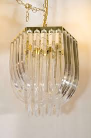 a set of three vintage lucite chandeliers with lucite prisms bent into loops and suspended