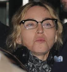 madonna sports quite an unusual look in this picture she chooses to play it safe in a simple outfit and her signature scarf her nerdy gles give her a