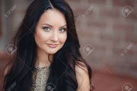 a beautiful young woman long thick brown hair gray green eyes light makeup and a nice smile spends time in the city in the summer sitting near near the