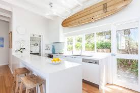 coastal style kitchen features a surfboard on wall over a bank of windows and white lacquered cabinets fitted with dual sink