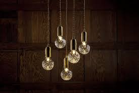 the clear crystal bulb chandelier features five clear crystal bulbs suspended at set lengths from a satin white ceiling plate and creates a dramatic cer