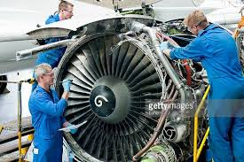 engineers assembling engine of passenger jet in hangar turbine engine mechanic