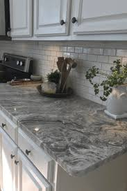 exposed white brick wall backsplash grey granite countertop plain white vas white kitchen cabinet with black