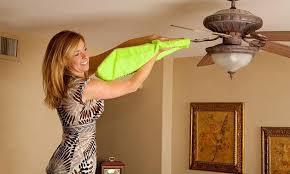 a women using fanbladecleaner to wipe off a fan blade