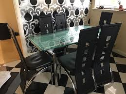 faux leather high back chairs. glass extendable dining table with 6 black faux leather high back chairs