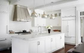 beautiful small white kitchen boasts three industrial light pendants hung above a statuary quartz countertop fitted with a farmhouse sink and a pull out
