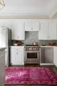 a hot pink kitchen runner leads to white raised panel cabinets adorned with brass pulls paired with white quartz countertops and a marble mosaic tiled