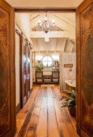 salvaged flea market doors lead from the bedroom into the en suite bathroom chandelier camilla chandelier barn board