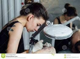 Young Girl Tattoo Master With Hair Tied In Bunch In Black Undershirt