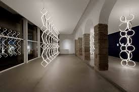 described by flos as being halfway between a sculpture and a piece of industrial design arrangements consists of a series of tubular elements in a variety