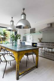 industrial kitchen with yellow table details at a Victorian house located  in the London Borough of Fulham kinda cool with the huge street light light  ...