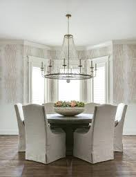 chandelier over table clear beaded chandelier over a round wood dining table with gray linen dining chandelier over table