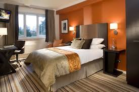 a classy bedroom that uses colorful striped floor carpet dark furniture and a large cabinet