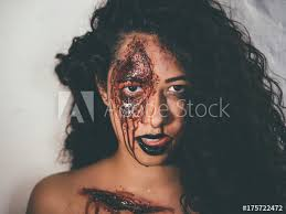 scary portrait of young zombie with blood makeup beautiful latin woman with curly hair looking into camera in studio living dead lady