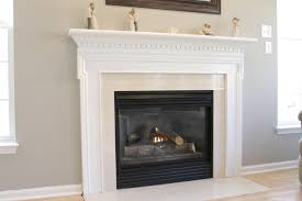 white fireplace mantel on top ceramics with black