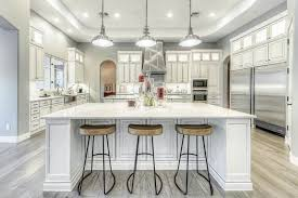 transitional kitchen with white cabinets and wood grain porcelain tile floors and industrial style pendant lights