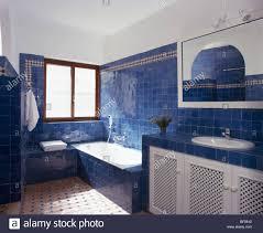 Bright blue tiles on wall above bath in modern Spanish bathroom