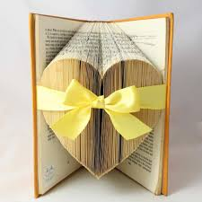 folded book art with yellow bow